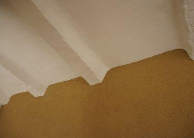 Pintura mineral blanca sobre vigas de hormigón reformadas y revestimiento de tierra fibrado